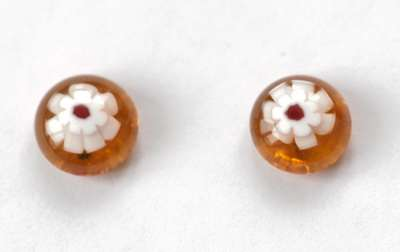 White flowers on amber. 10 mm